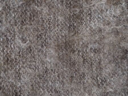 Fragment of a knitted fabric of a fluffy shawl handmade from natural goat hair of brown color. View from above. Horizontal frame.