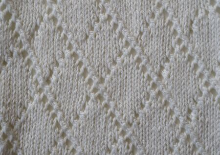 Fragment of a knitted fabric of openwork manual knitting from white yarn. View from above. Horizontal frame.
