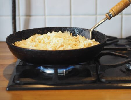 Home cooking. Fried cabbage in oil in a black frying pan on the stove. Nearby fried fish. The stage of preparation of the filling for the pie. Cooking.