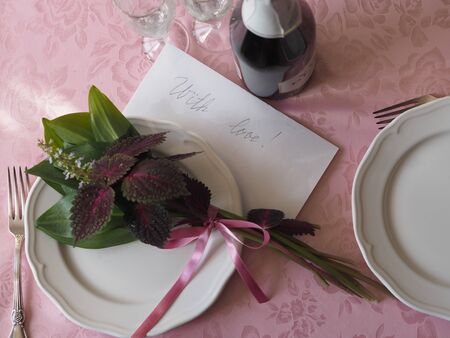 Top view, on a pink tablecloth, a bouquet of green leaves and Coleus red flower on a white plate. Letter with the inscription with love and two wine glasses for wine. Place for text.
