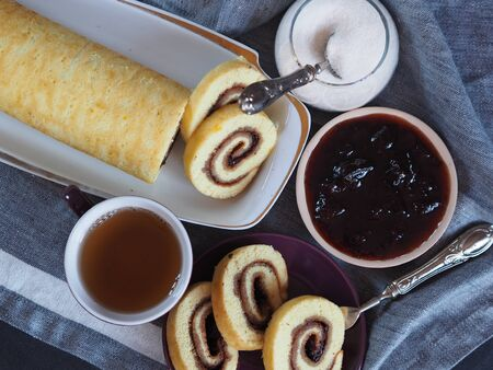 Homemade biscuit sponge roll with sweet plum jam and tea against a dark background. Natural homemade dessert. Top view.