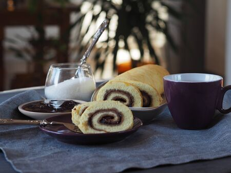Homemade biscuit sponge roll with sweet plum jam and tea against a dark background. Natural homemade dessert. Side view. Background blurred image of a kitchen.