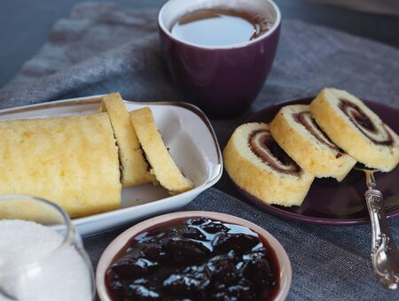 Homemade biscuit sponge roll with sweet plum jam and tea against a dark background. Natural homemade dessert. Side view.