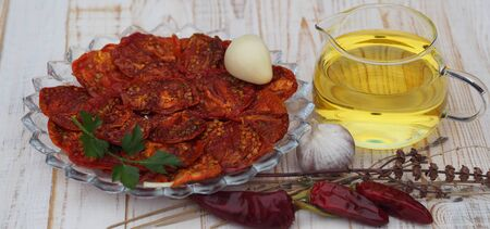 The concept of healthy eating.The benefits of dried fruits and vegetables. Dried tomato vegetable chips with ingredients for cooking on a wooden table.