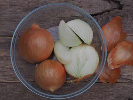 Fresh Golden onion bulbs. Onion in a glass plate on a wooden rustic ancient background.Health benefits of onions and the use of their skins for coloring eggs at Easter.