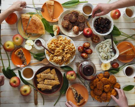 A festive meal of preparation for Easter on a white wooden table with homemade cakes. Meeting friends who have healthy natural food. Flat position of the table with hands of food and people eating. The view from the top.. Imagens - 143138333