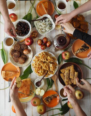 A festive meal of preparation for Easter on a white wooden table with homemade cakes. Meeting friends who have healthy natural food. Flat position of the table with hands of food and people eating. The view from the top.. Imagens