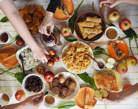 A festive meal of preparation for Easter on a white wooden table with homemade cakes. Meeting friends who have healthy natural food. Flat position of the table with hands of food and people eating. The view from the top.. Imagens - 143138351