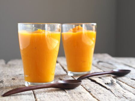 Health benefits of pumpkin. Pumpkin pulp passed through a blender. Eco-friendly smoothie cooked at home on a wooden table and gray background. Home cooking.