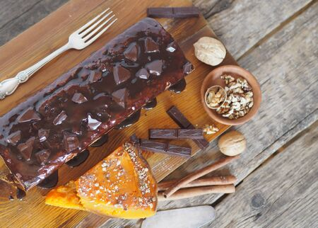 Place for text. Holiday homemade chocolate pumpkin long rectangular cupcake, glazed with chocolate, ready to eat on a kitchen board. Wooden background.
