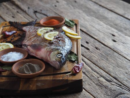 Close-up. Raw river fish of bream cooked for baking in the oven with slices of lemon and seasoning on a wooden board. Front view.