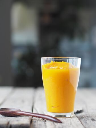 A glass of natural smoothie, juice, cocktail made at home from the pulp of homemade pumpkin, on a blurred kitchen background. Health benefits of pumpkin. Stock Photo