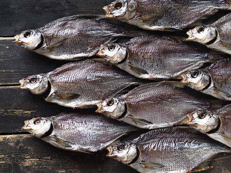 Fish background.A lot of air-dried, salty freshwater bream on a dark wooden ancient table.River fish.