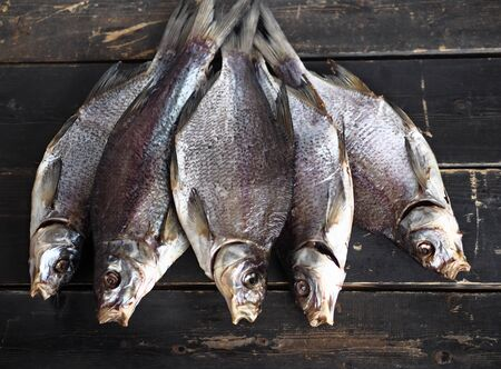 Air-dried,privately owned, freshwater river fish bream, on a dark wooden table.Close up.An intimidating sight, with an open mouth. Stockfoto