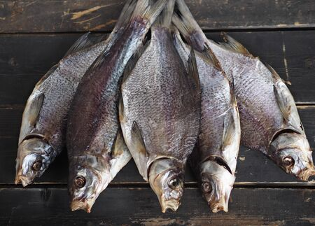 Five dried freshwater river bream fish on a dark wooden rustic table.