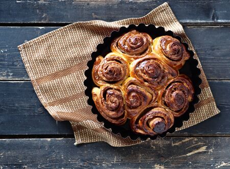 Home cooking. Freshly baked rolls in a red baking dish with a napkin on a dark wooden background.