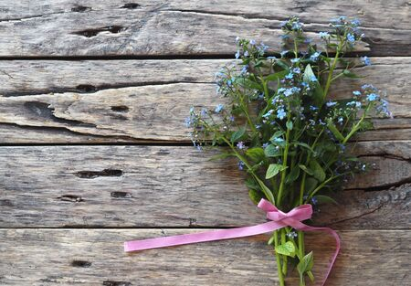 Floral background. Bouquet of tender blue forget-me-nots on a wooden ancient table. Place for text.