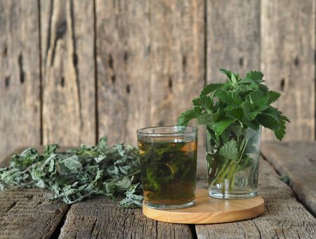 Drug plants. Herbal tea with dried Melissa or mint on a natural wooden table.
