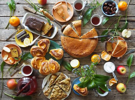 Festive meal on an ancient wooden table. A table with natural homemade cakes, fruits is ready to receive guests Standard-Bild