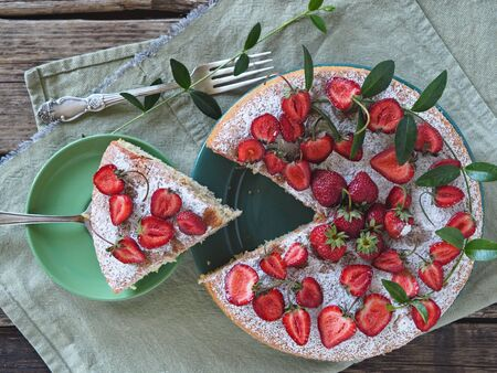 Close-up. Spring berry cake with strawberries upstairs on a wooden background. View from above.