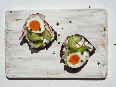 Food background.Healthy toasts with whole grain bread, cucumber, radish and boiled egg on a wooden board in the kitchen.