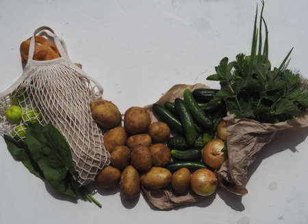 Place for text. Natural agricultural products cucumbers, potatoes, onions, greens, green apples with a bag with bread on a light background. No plastic.