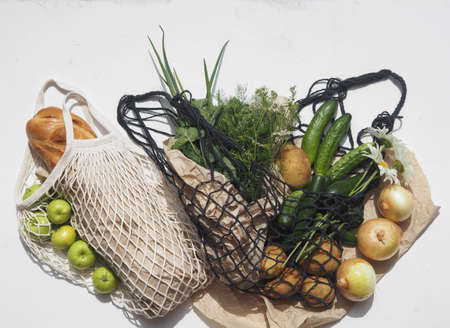 Place for text. Bread and agricultural products, vegetables in knitted bags on a white background. No plastic.