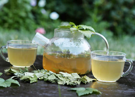 Tea in a glass teapot with leaves of black currant, berries and green leaf on a background bamboo napkin