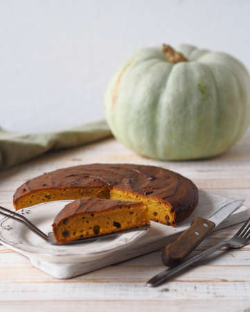 Homemade pumpkin pies.Rustic cooking style. Pumpkin muffin on a white rustic plate with a kitchen napkin and a large pumpkin in the background. Stock Photo