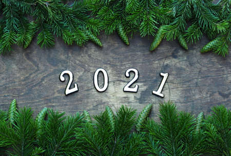 Happy New Year 2021. Branches of a Christmas tree are laid out on a wooden background. New year background with numbers 2021.