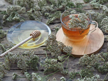 Medicinal herbs.Yarrow herbal tea in a glass cup with honey on a wooden natural background.