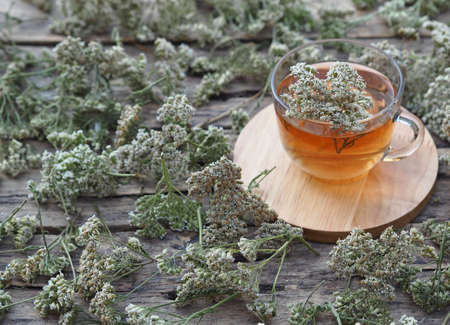 Herbal medicinal background.Healthy tea with yarrow flowers on a wooden rustic table. Place for text.
