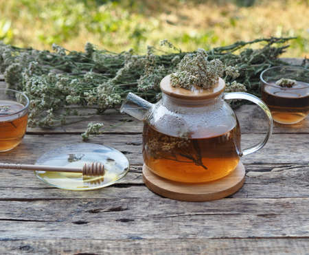 Herbal medicinal background.Healthy tea with yarrow flowers in a teapot with cups and honey on a wooden rustic background.