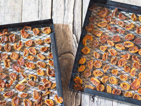 Procurement of dried apricots for future use.Dried apricots in a rack from the dryer on a wooden natural table.