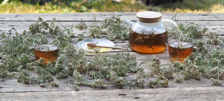 Medicinal herbs.Yarrow herbal tea in a glass teapot with a cup of honey on a wooden natural background.