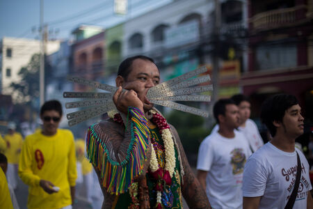 pierce: PHUKET, THAILAND ? October 1: Unidentified Mah song pierced weapon to their cheeks, They believed to suffer the pain of devotee during the Phuket Vegetarian Festival. The Festival is a famous annual festival also known as Nine Emperor Gods festival on the