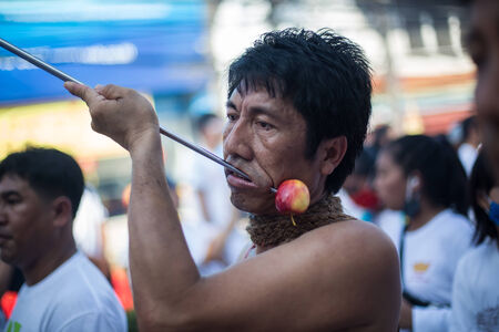 formidable: PHUKET, THAILAND ? October 1: Unidentified Mah song pierced weapon to their cheeks, They believed to suffer the pain of devotee during the Phuket Vegetarian Festival. The Festival is a famous annual festival also known as Nine Emperor Gods festival on the