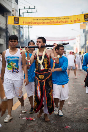 god walking: PHUKET, THAILAND - SEPTEMBER 30: Unidentified Mah song pierced weapon to their cheeks, They believed to suffer the pain of devotee during the Phuket Vegetarian Festival. The Festival is a famous annual festival also known as Nine Emperor Gods festival on  Editorial