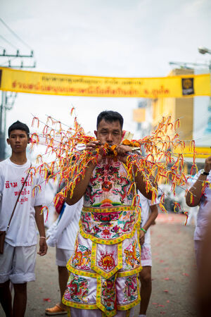formidable: PHUKET, THAILAND - SEPTEMBER 30: Unidentified Mah song pierced weapon to their cheeks, They believed to suffer the pain of devotee during the Phuket Vegetarian Festival. The Festival is a famous annual festival also known as Nine Emperor Gods festival on  Editorial