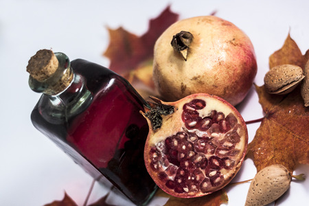 autumn bodegon of liquor, grapes, almonds, pomegranate and dried leaves