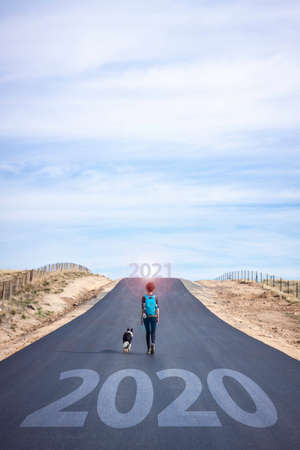 Start a new year. Leave behind 2020. Lifestyle photography, woman with dog on the road in search of adventure 免版税图像
