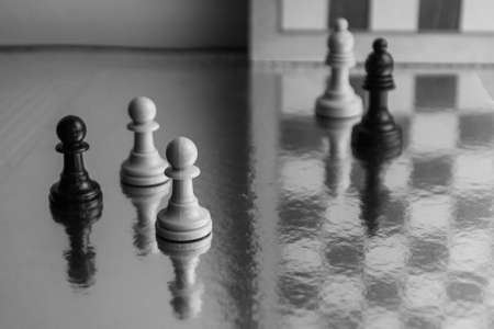 Photograph of black and white chess pieces. Strategy game. Pawns with reflections on original background