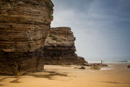 Cathedrals Beach in Ribadeo, Galicia. Low tide in summer. Cliff of rocks forming arches