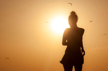 Silhouette young woman enjoying on the beach with a sunny sunset. Carefree person enjoying on vacation Reklamní fotografie