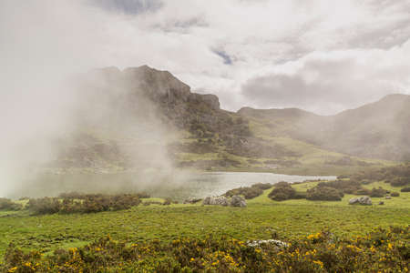 Lakes of Covadonga with fog in Spring. Tourists hiking on Lake Enol. Asturias, Spain Reklamní fotografie