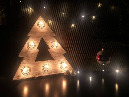 Wooden Christmas tree with lamps. Christmas toys on the table. Merry Christmas. Фото со стока