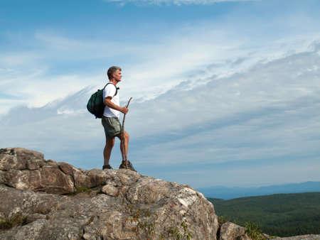 Un uomo di età adulta in piedi sulla cima della montagna