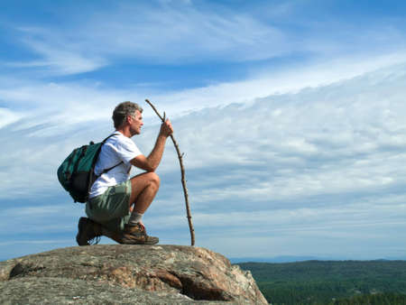 Mature Adult Man kneeling on rocky mountaintop photo