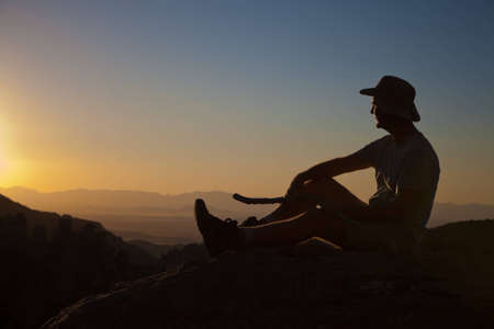 hiking boot: Mature man rest from hikingto enjoy the sunset on top of a mountain