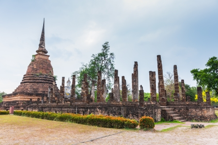 colonade: ancient seated buddha staue in the temple ruins of sukhothai in thailand Stock Photo